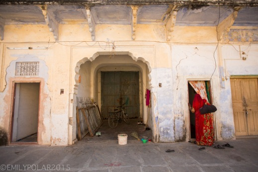 Indian woman standing in a doorway wearing a red sari in Pushkar, India.