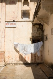 White sheets drying on a clothes line near a temple in Pushkar, India.