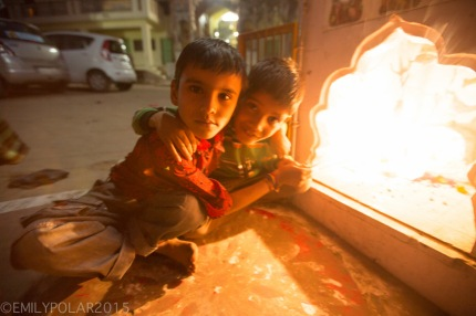 Indian boys make offering burning incense in a mini alter on the streets of Pushkar.