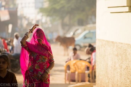 Indian woman walking down a sunny dusty street in Pushkar wearing a colorful pink Sari with her head covered.