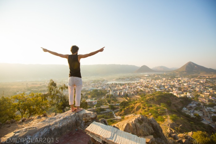 Western tourist walking along a stone wall in the warm light of  sunrise at the Gayatri Temple in Pushkar, India.