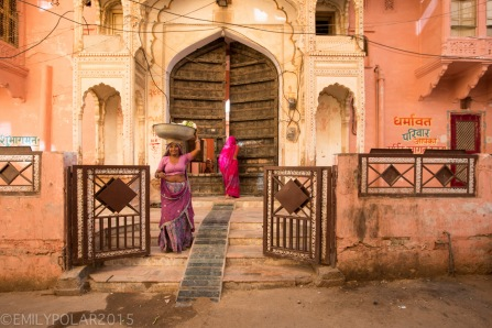 Indian woman carrying a metal bowl on her head walking into the streets from her home in Pushkar.