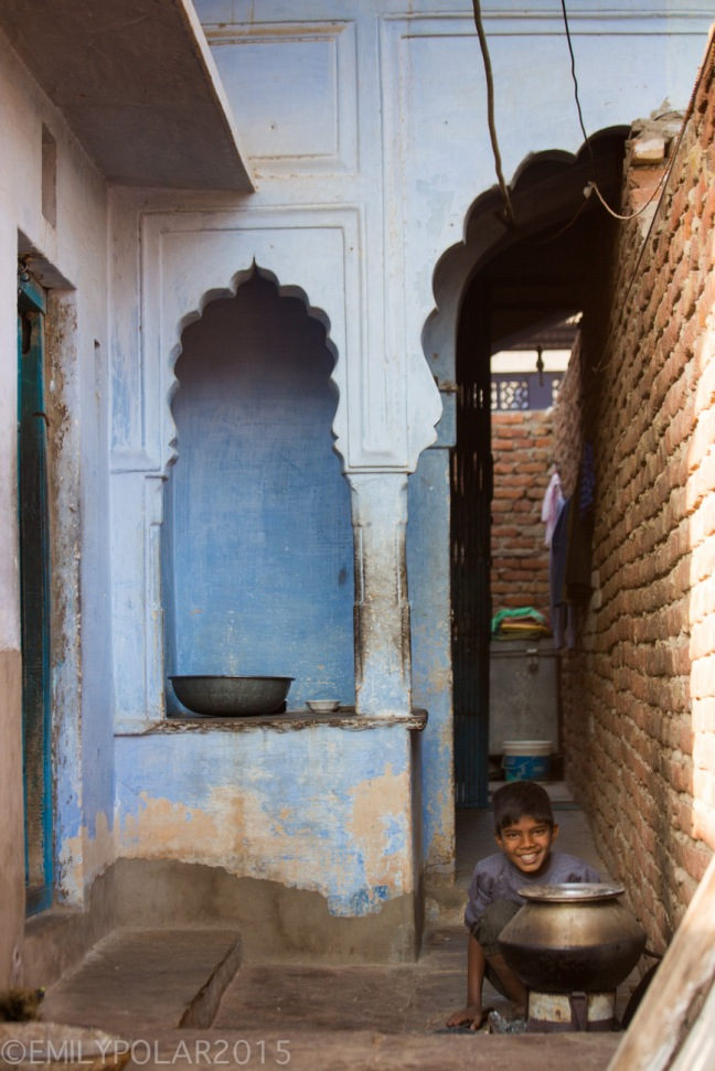 Young boy sitting outside the doorway to his house cooking in a steel pot in the blue of Pushkar in Rajasthan.