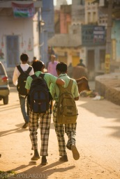 Two young boys wearing uniforms and backpacks walk to school together in the morning down a dusty street in Pushkar.
