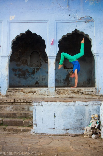 Woman doing handstands in the blue arches in Pushkar, Rajasthan.