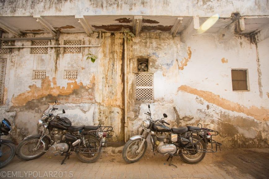 Old motorcycles parked in front of a old wall in the streets of Pushkar.