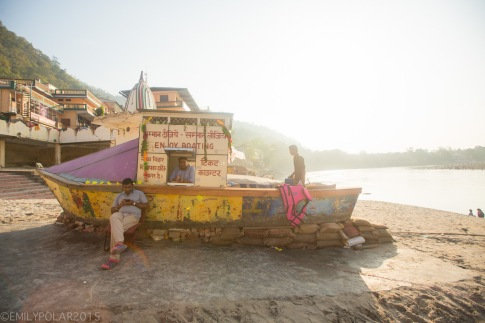 Wooden boat docked on the banks of the Ganges river selling tickets for boat rides in Laxman Jhula Rishikesh.