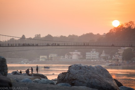 Locals and tourists hang out on the sandy beach along the Ganges river at sunset near the Ram Jhula bridge in Rishikesh.