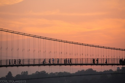 People crossing Ram Jhula bridge with golden ball of sun setting behind the trees along the Ganges River.