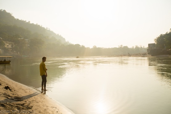 Young Indian man standing at the shore of the Ganges river in Rishikesh.