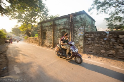 Tourist riding scooter down the road in Rishikesh, India.