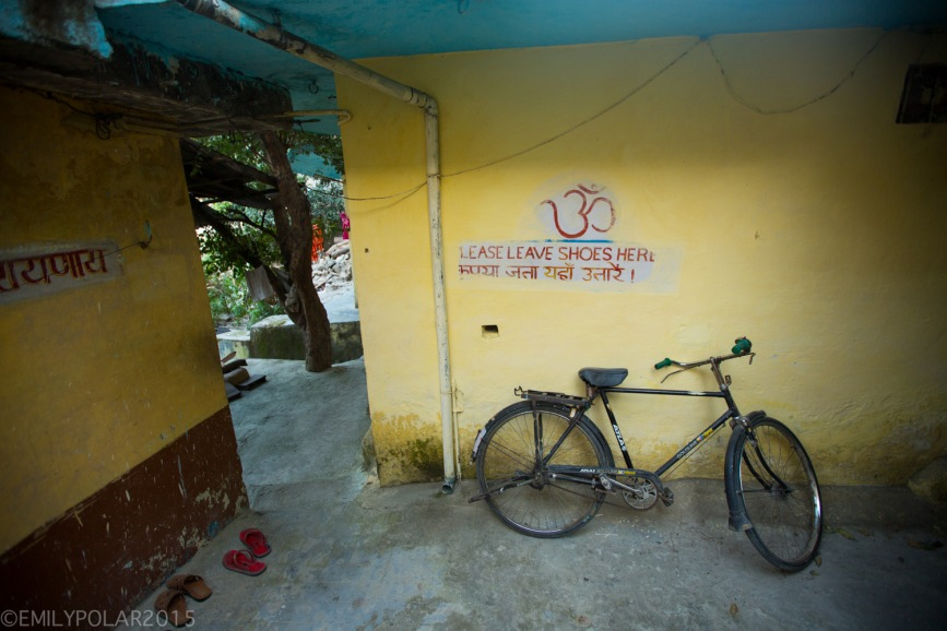 Bike parked at the entrance of an home with a painted sign to take shoes off.