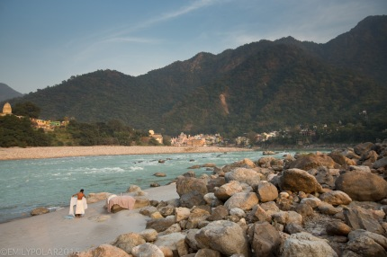Indian man dressing on the banks of the Ganges river after washing in the holy river in Rishikesh.
