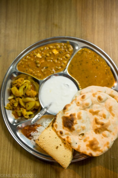 Standard Veg Thali Set plate with rice, veg, lentils and muttar paneer, chapati, roti, and curd.