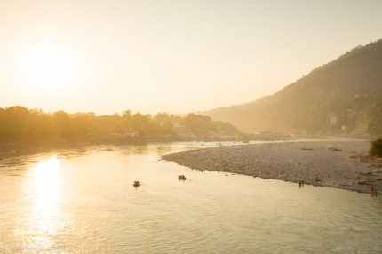 Red rafts float down the Ganges at sunset past the north side of Laxman Jhula bridge in Rishikesh, India.