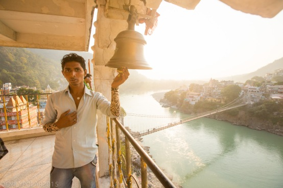 Man ringing bell at Lakshman Temple at sunset in Rishikesh, India.