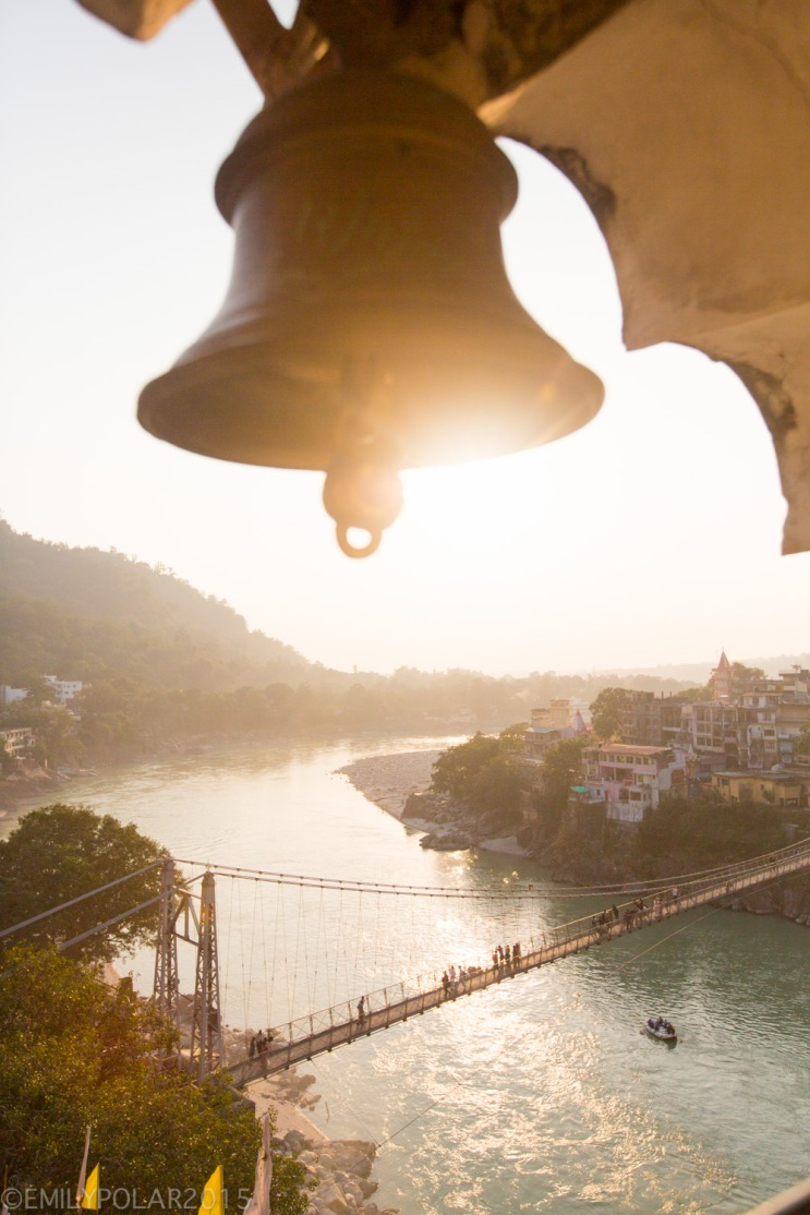Sun setting over the Ganges behind Laxman Jhula bridge in Rishikesh, India.