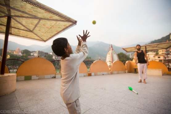 Young Indian boy plays catch with a Western Tourist in Laxman Jhula, Rishikesh.