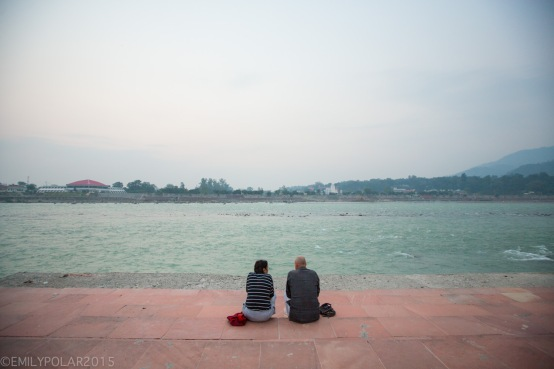 Couple sitting along the Ganges at dusk in Rishikesh, India.