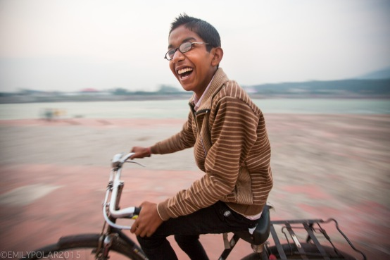 Yound Indian boy riding bicycle with glasses and a big smile at the Ghat near Ram Jhula, India.