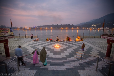 Families walking down stairs to the Ghat for puja at sunset near Ram Jhula in India.
