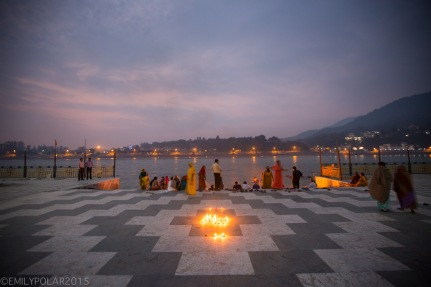 Families lighting candles and oil filre at the Ghat along the Ganges for puja at sunset near Ram Jhula in India.