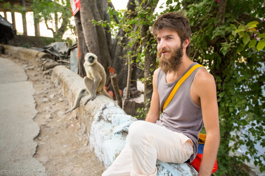 Traveler with big beard sitting next to monkey copying his posture in the streets of Rishikesh.