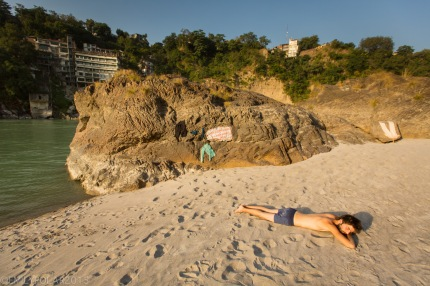 Western man laying out in the sun on a sandy beach at Hanuman rock in Rishikesh, India.
