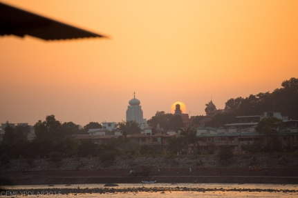 Golden ball of light that is the sun setting behind the holy buildings along the Ganges in Rishikesh.