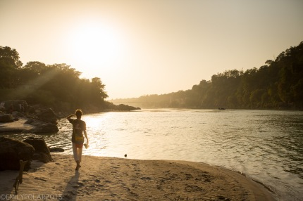 Man walking along the Ganges in the sand into the golden sunset in Rishikesh, India.