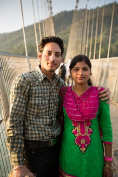 Cute Indian couple pose for a photo on the Ram Jhula bridge in Rishikesh, India.