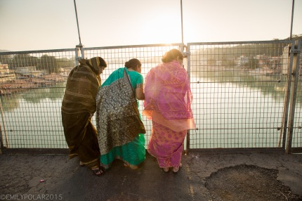 Indian women look out from Ram Jhula bridge in Rishikesh, India.