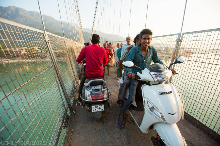 Young Indian boys driving a scooter across Ram Jhula Bridge in Rishikesh, India.