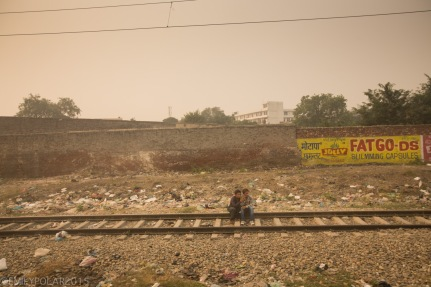 Boys sitting on the railroad tracks in the middle of nowhere in Northern India.
