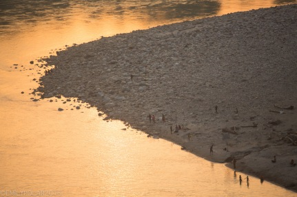 Locals and tourists gather at the shores of the Ganges river at sunset in Rishikesh.