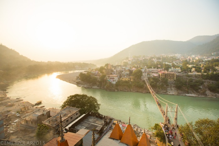 Aerial shot of Laxman Jhula bridge over the Ganges among holy Hindu temples of Rishikesh, India.