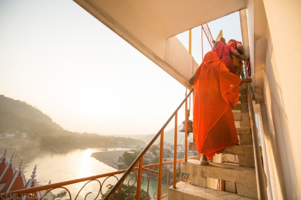 Woman in red sari walking up stairs of Trayambakeshwar Temple in Rishikesh, India.