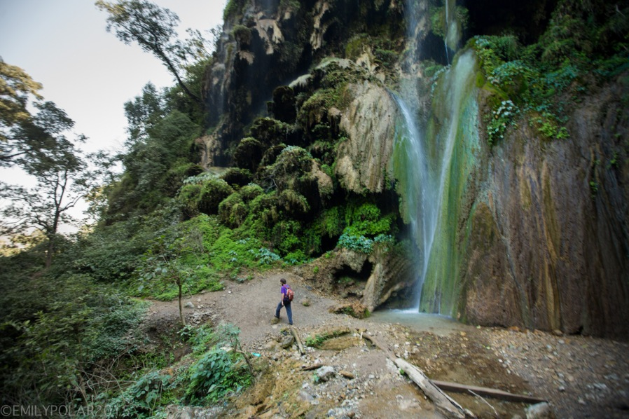 Man walking along the base of the Patna Waterfall in the lush forest of Uttarakhand near Rishikesh.