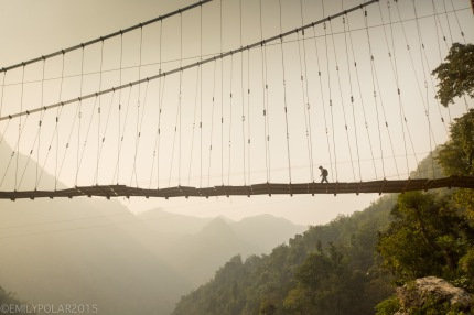 Boy walking across old bridge through the haze high above the ganges river in Uttarakhand state India.