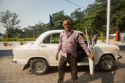 Hindu man getting out of his white taxi in the streets of Rishikesh, India.