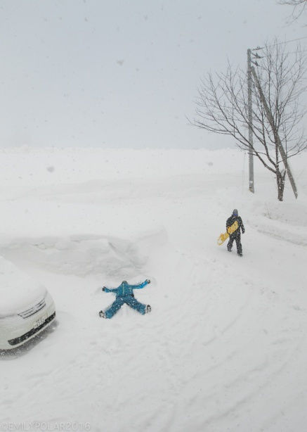 Man making snow angel in the parking lot full of snow in Niseko, Japan.