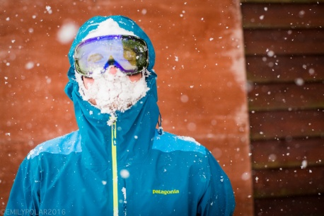 Powder portrait of a snowboarder in a blue jacket with goggles and a face covered in snow.