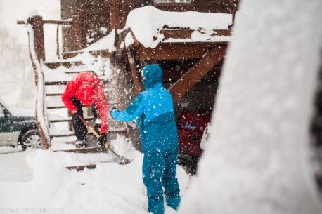 Snowboarders shoveling snow off the stairs while playing in the endless powder of Japan, Niseko.