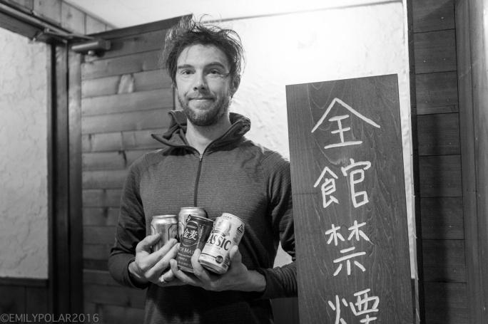 Man buying beer out of a vending machine in Niseko, Japan.