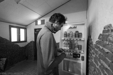 Man buying beer out of a vending machine in Niseko, Japan.