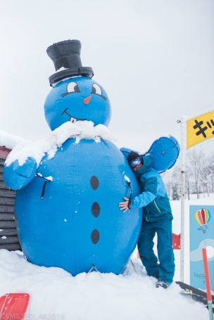 Snowboarder standing with huge blue snowman at the base of Annupuri resort.