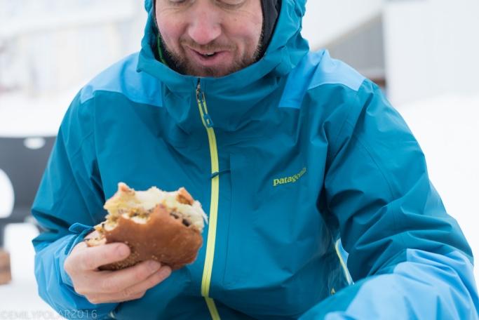 Man eating a cheeseburger at the base of Annupuri mountain in Niseko, Japan.