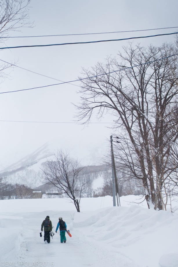 Snowboarders walking down snowy road near the base of Annupuri in Niseko, Japan.