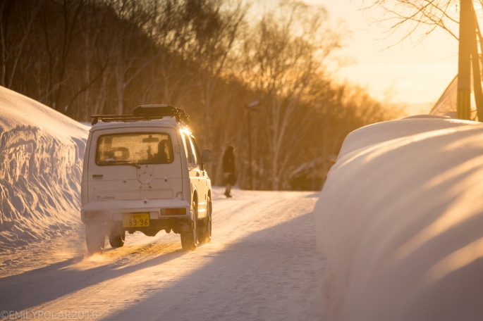 Jeep driving down a snowy road into the warm glowing sunrise in Niseko, Japan.