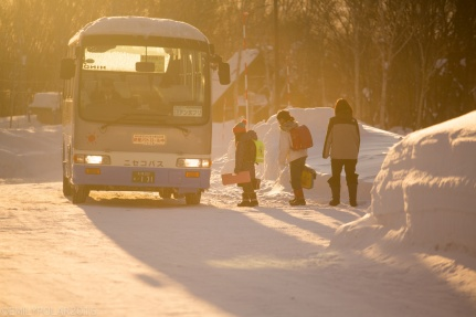 Kids getting on the bus at sunrise in snowy Niseko, Japan.